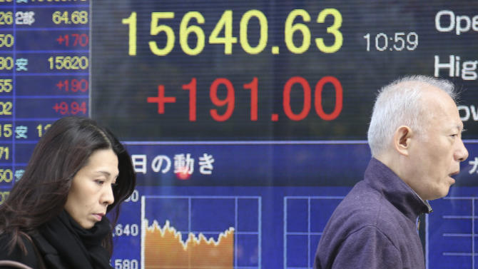 People walk by an electronic stock board of a securities firm in Tokyo, Thursday, Nov. 28, 2013. Japanese stocks jumped on Thursday as the yen lingered near a six month low, leading a broader advance by Asian markets after U.S. benchmarks rose to record levels. (AP Photo/Koji Sasahara)