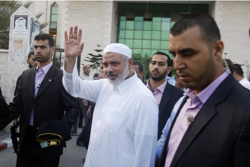 Surrounded by security guards, Gaza's Hamas Prime Minister Ismail Haniyeh, center, waves as he arrives for the Eid al-Fitr prayers in Khan Younis, southern Gaza Strip,Tuesday, Aug. 30, 2011. Muslims are celebrating the festival of Eid al-Fitr which marks  the end of the holy fasting month of Ramadan.(AP Photo / Hatem Moussa)