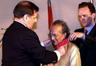 Indian sitar maestro Pandit Ravi Shankar (C) receives France's highest civilian award, the Commander of the Legion of Honor from then the French Ambassador to India, Claude Blanchemaison (L), on February 12, 2000