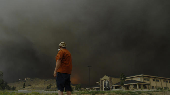 A man stops quickly to get some video before running away from approaching flames of the Waldo Canyon Fire as it raced down into western portions of Colorado Springs, Colo. on Tuesday, June 26, 2012 leaving a trail of destruction and burning homes and buildings in its path. Heavily populated areas in the fire's path have been affected.   (AP Photo/Bryan Oller)