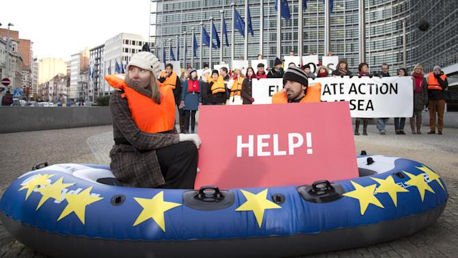 Protestors from Friends of the Earth hold up cards during a demonstration outside EU headquarters in Brussels on Wednesday, Jan. 22, 2014. The European Commission on Wednesday proposed a framework for climate and energy policies beyond 2020 and up to 2030. (AP Photo/Virginia Mayo)