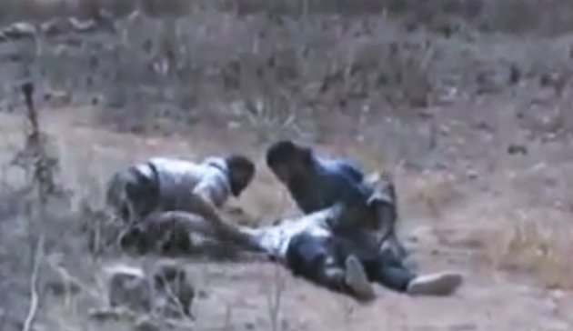 This image made from amateur video released by Ugarit News and accessed Thursday, June 21, 2012, purports to show Syrians helping a wounded man at Baba Amr neighborhood in Homs Province, Syria. A spok