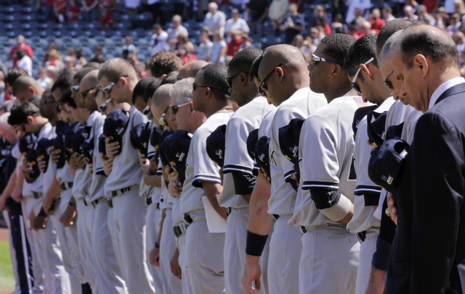 Members of the New York Yankees stand during a ceremony to commemorate the Sept. 11, 2001 anniversary prior to the Yankees baseball game against the Los Angeles Angels, Sunday, Sept. 11, 2011, in Anaheim, Calif. (AP Photo/Mark J. Terrill)
