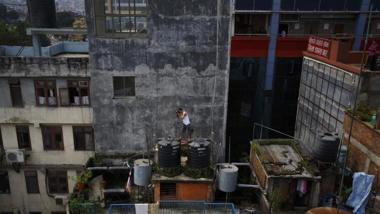 A man takes pictures on a house roof in Kathmandu
