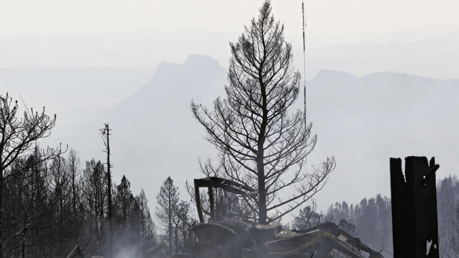 Smoke rises through a torched area during a wildfire burning in the foothills community of Conifer, Colo., southwest of Denver on Tuesday, March 27, 2012. Firefighters are now able to actively battle the blaze on the ground that started on Monday and has already destroyed at least 23 structures and caused the deaths of two people. (AP Photo/Ed Andrieski, Pool)