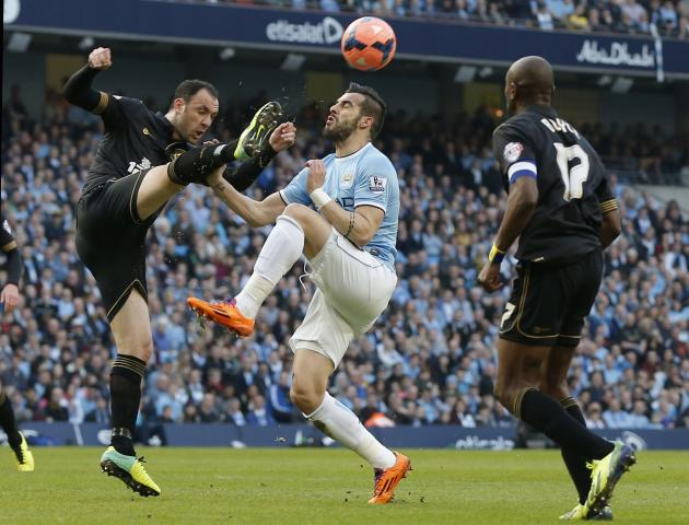 Wigan Athletic's Ramis challenges Manchester City's Negredo during their English FA Cup quarter final soccer match at the Etihad stadium in Manchester