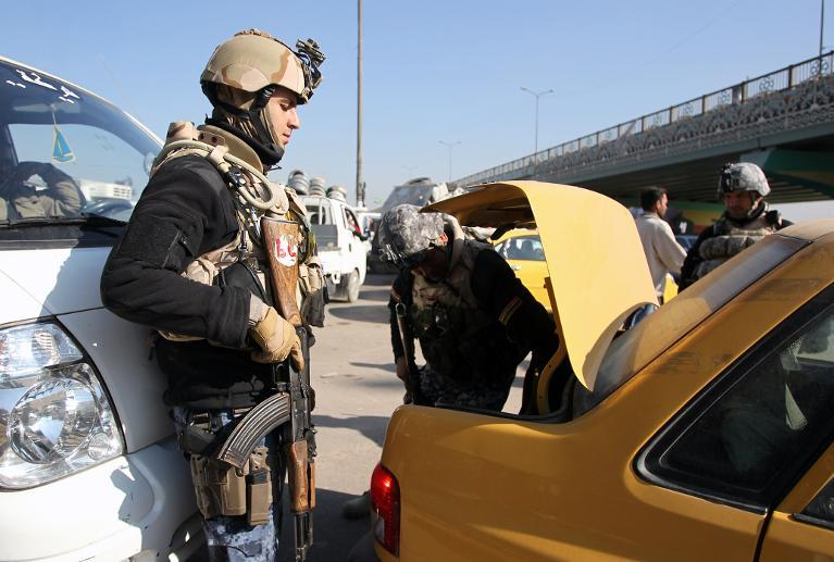 Iraqi security forces search the boot of a car at a checkpoint in Baghdad, on December 16, 2013