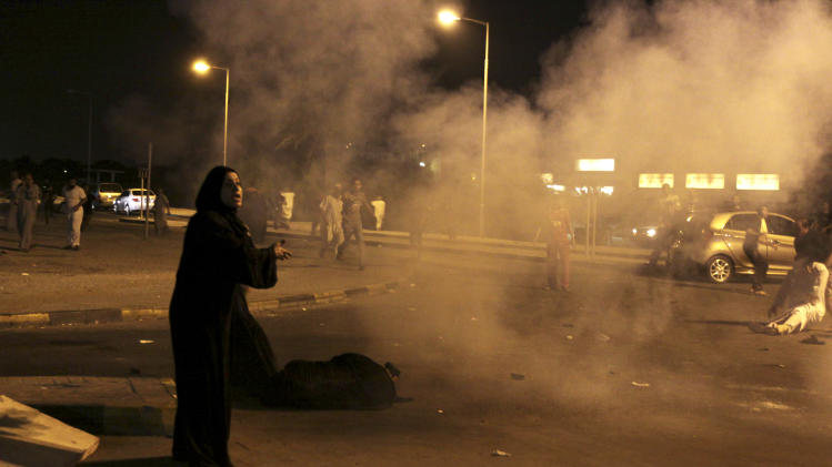 "A Bahraini woman shouts at riot police, unseen, to stop firing as residents help those who fell during the barrage of tear gas and stun grenades aimed at dispersing villagers gathered in Sadad, Bahrain, early Saturday, Sept. 29, 2012, at the scene where a youth was killed, allegedly by police shotgun fire. An Interior Ministry statement said a police patrol was attacked with petrol bombs and iron rods late Friday, and one person died when ""policemen defended themselves."" A witness among protesters said demonstrators were marching against the government when a policeman suddenly stepped out near the youth and shot him at close range. (AP Photo/Hasan Jamali)"