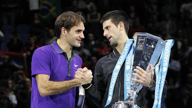 Novak Djokovic, right, of Serbia holds the winners ATP World Tour tennis trophy as he shakes hands with runner-up Roger Federer of Switzerland during the presentation ceremony following their singles final match in London, Monday, Nov. 12, 2012. (AP Photo/Sang Tan)