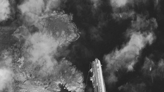 This picture made available on Wednesday, Jan. 18, 2012 by DigitalGlobe, satellite image made on Tuesday, Jan. 17, 2012,  shows the hulk of the luxury cruise ship  Costa Concordia, which ran aground the Tuscan tiny island of Isola del Giglio, Italy, on Friday, leaning on its starboard side. As the Costa Concordia keeps shifting on its rocky ledge, many has raised the prospect of an environmental disaster if the 2,300 tonnes of fuel on the half-submerged cruise ship leaks. Satellites are used to monitor the area while authorities are preparing to remove the fuel from inside the vessel. (AP Photo/DigitalGlobe)  MANDATORY CREDIT