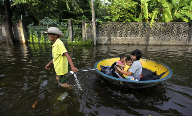 A Thai man pulls a makeshift boat to carry a his family through a flooded street in Bangkok, Thailand, Saturday, Nov. 5, 2011. Floodwaters lapped Bangkok's largest outdoor market Saturday as officials