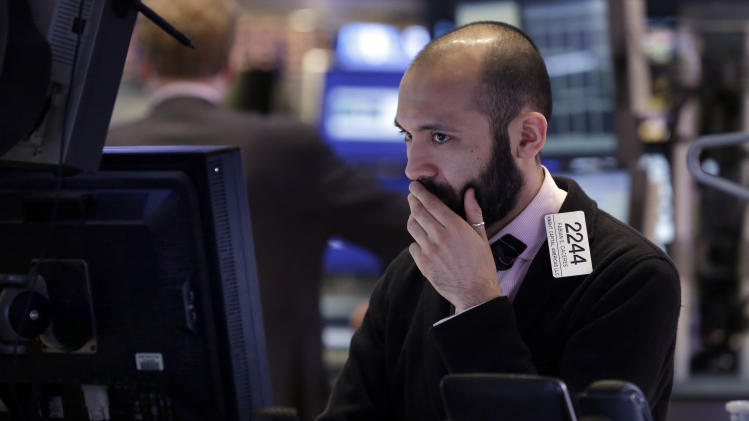 Specialist Fabian Caceres works on the floor of the New York Stock Exchange Wednesday, Jan. 30, 2013.  Stocks are falling after the government revealed that economic growth shrank in the final quarter of 2012, the first time that's happened in more than three years. (AP Photo/Richard Drew)