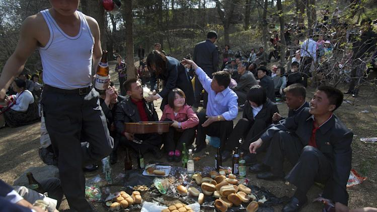 FILE - In this April 18, 2012 file photo, North Koreans enjoy a picnic on a hilltop park overlooking Pyongyang on a national holiday celebrating the birthday period of the late leader Kim Il Sung. In the supposed workers' paradise of North Korea, inequality is assigned at birth, according to a study released Wednesday, June 6, 2012, by a U.S.-based human rights group. Education, jobs, access to scarce food and health care and even whom you marry all hinge on how loyal your forebears are viewed to have been to the Kim dynasty that took power six decades ago.  (AP Photo/David Guttenfelder, File)