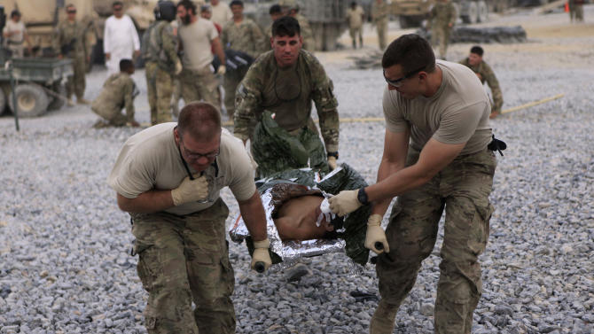 """U.S. soldiers carry an Afghan boy wounded by a roadside bomb to a medevac helicopter from the U.S. Army's Task Force Lift """"Dust Off"""", Charlie Company 1-52, on the outskirts of Kandahar, Afghanistan, Thursday, July 28, 2011.(AP Photo/Rafiq Maqbool)"""
