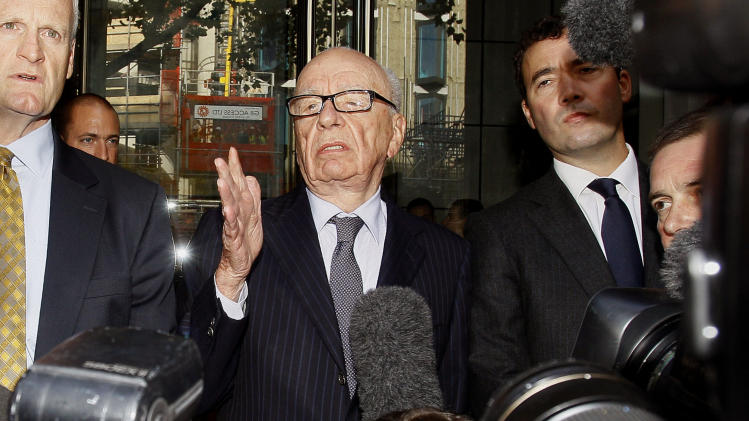 "Rupert Murdoch, centre, attempts to speak to the media after he held a meeting with the parents and sister of murdered school girl Milly Dowler in London, Friday, July 15, 2011. The lawyer for Milly Dowler's family says Rupert Murdoch has issued a full and sincere apology to the murdered schoolgirl's family for the actions of journalists at his newspaper. Mark Lewis told reporters that the media baron called the private meeting and apologized ""many times,"" telling the Dowlers the events that transpired at the News of the World tabloid were not in keeping with the standards set out when his own father entered the media industry. (AP Photo/Kirsty Wigglesworth)"
