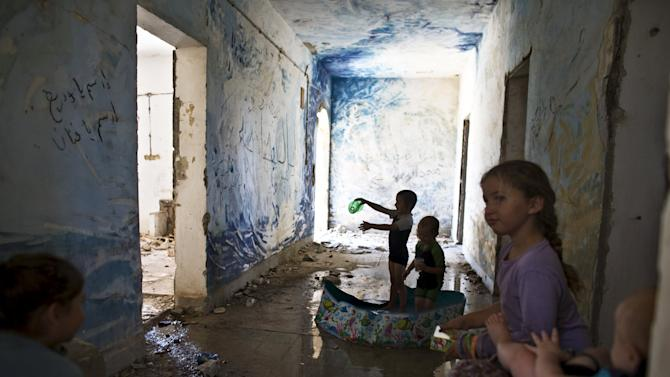 Children play in a plastic pool inside an abandoned building at the evacuated settlement of Sa-Nur in the West Bank