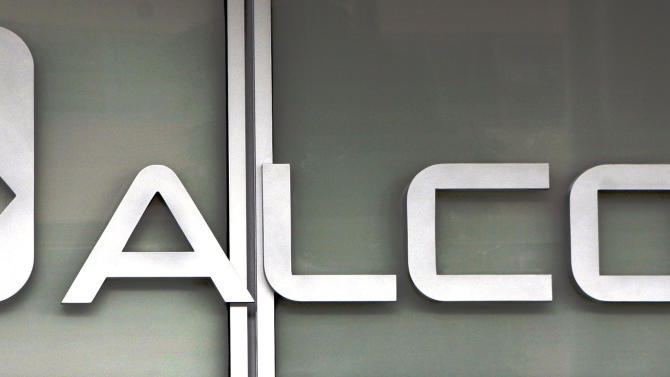 This April 9, 2011 photo, shows the Alcoa headquarters building logo in downtown Pittsburgh. Aluminum manufacturer Alcoa Inc. says Tuesday, Oct. 9, 2012, it lost $143 million in the third quarter due to charges, but otherwise topped Wall Street's expectations. Alcoa said Tuesday that the loss amounted to 13 cents per share. That compares with net income of $172 million, or 15 cents a share, a year ago. (AP Photo/Gene J. Puskar)