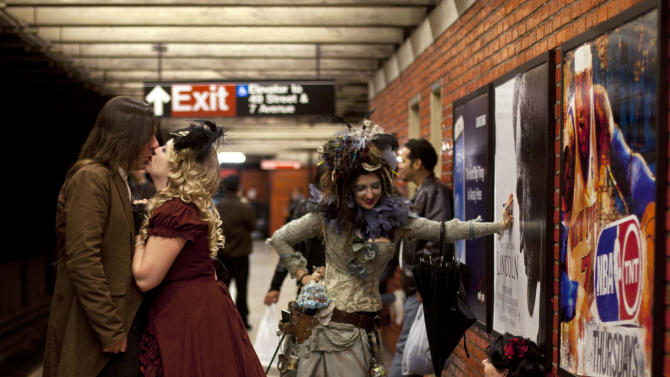 A couple in costume kisses on the platform edge of 49th Street metro station early Sunday, Oct. 28, 2012, in New York, in celebration of Halloween. (AP Photo/CX Matiash)