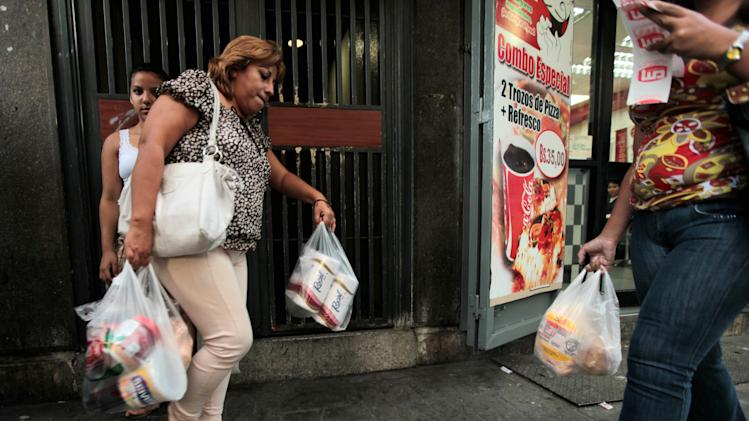 A customer leaves a private super market with her purchases, including toilet paper, in Caracas, Venezuela, Wednesday, May 15, 2013. First milk, butter, coffee and cornmeal ran short. Now Venezuela is running out of the most basic of necessities _ toilet paper. Blaming political opponents for the shortfall, as it does for other shortages, the embattled socialist government says it will import 50 million rolls to boost supplies. (AP Photo/Fernando Llano)
