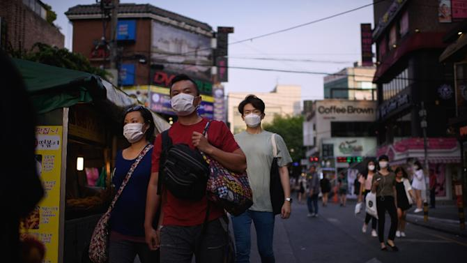 People with face masks are seen on a street in Seoul, on June 9, 2015