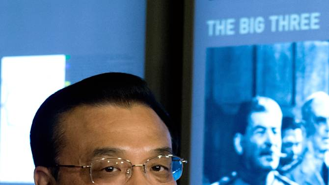 Chinese Prime Minister  Li Keqiang, stands in front of a historical photo  showing  Soviet leader Joseph Stalin, during his  visit at  Cecilienhof Castle  where,  after WWII  in 1945,  the Potsdam  Conference of the Allies  took place, in Potsdam, Germany Sunday May 26. 2013.   (AP Photo/ Soeren Stache, Pool)