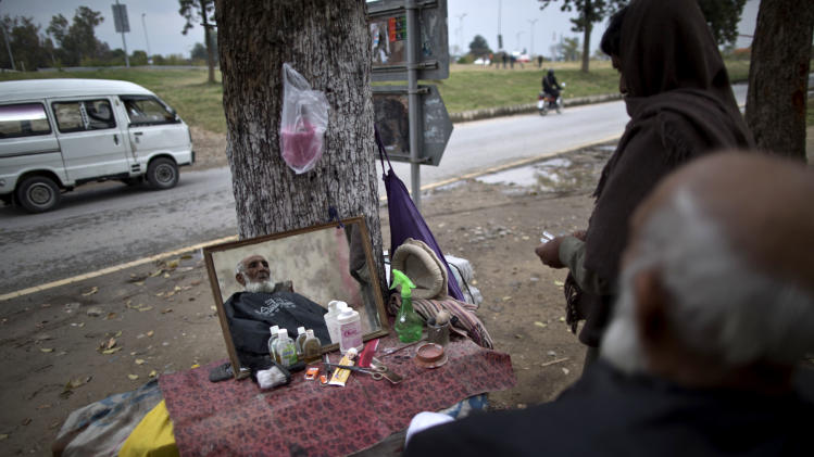 An elderly Pakistani man has his beard groomed for 30 Rupees (U.S. 30 cents), at a street barber in Islamabad, Pakistan, Monday, March 10, 2014. (AP Photo/Muhammed Muheisen)