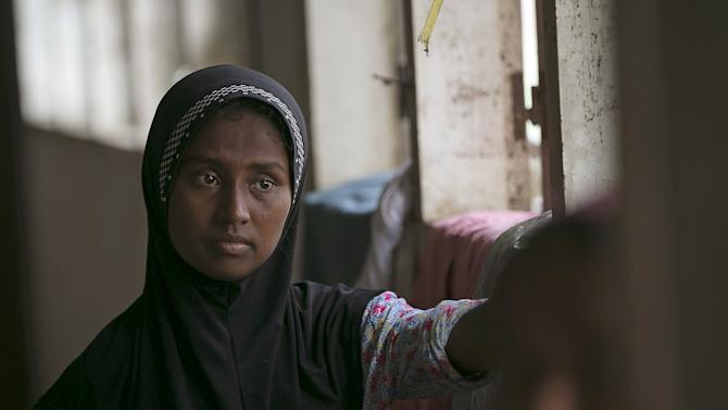 A Rohingya migrant, who arrived in Indonesia this week by boat, stands inside a temporary shelter in Aceh Timur