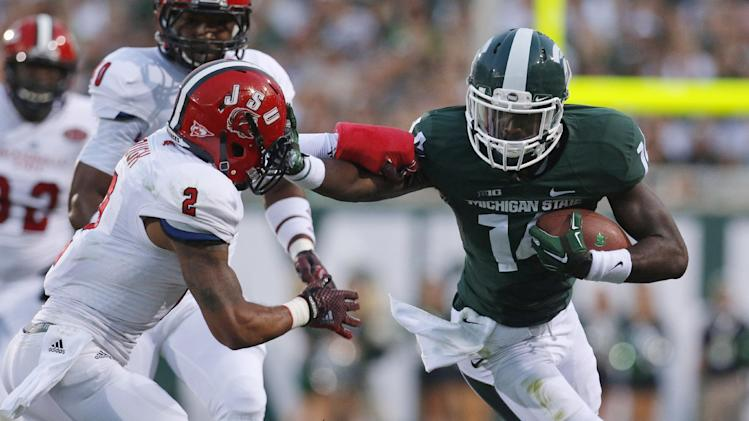 Michigan State's Tony Lippett, right, stiff-arms Jacksonville State's Jermaine Hough (2) during the first quarter of an NCAA college football game, Friday, Aug. 29, 2014, in East Lansing, Mich. (AP Photo/Al Goldis)