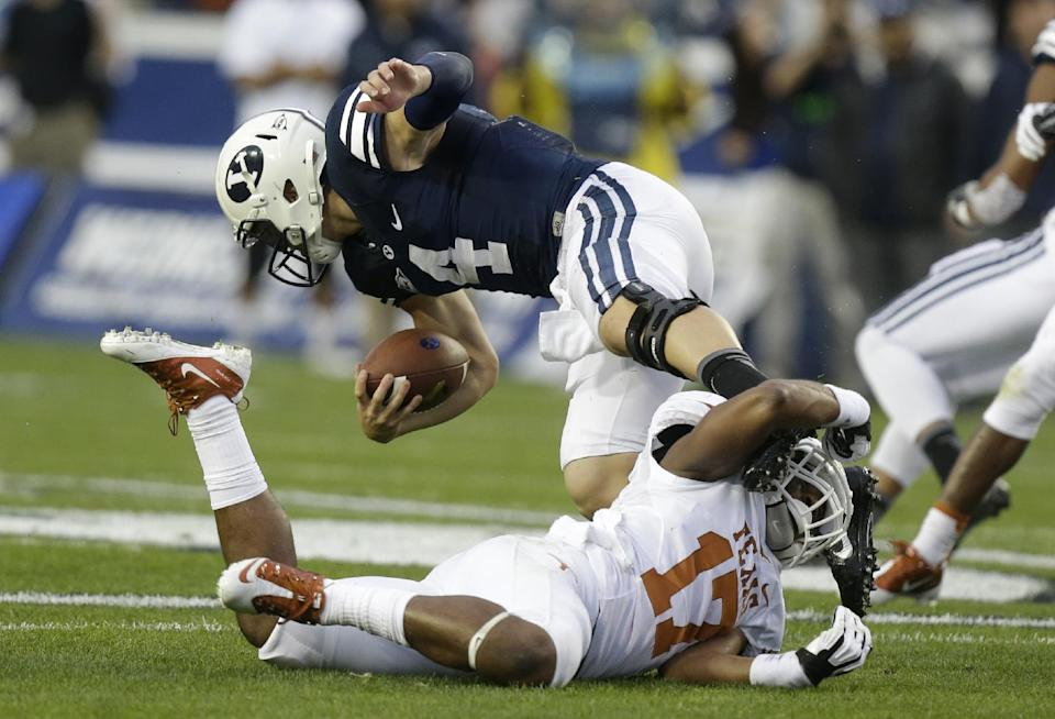 Texas safety Adrian Phillips (17) tackles Brigham Young quarterback Taysom Hill (4) in the first half during an NCAA college football game Saturday, Sept. 7, 2013, in Provo, Utah. (AP Photo/Rick Bowmer)