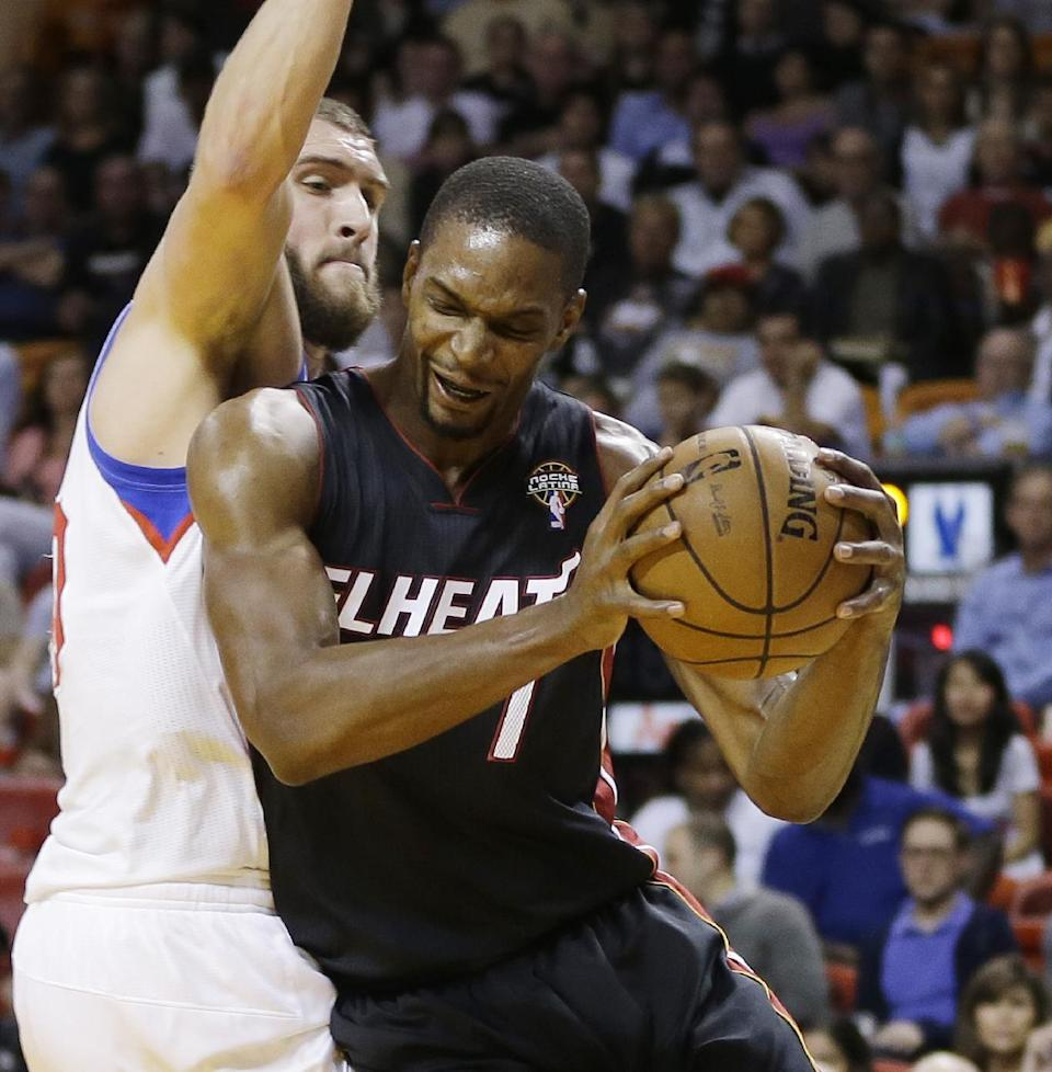 Philadelphia 76ers' Spencer Hawes (00) defends Miami Heat's Chris Bosh (1) during the first half of a NBA basketball game in Miami, Friday, March 8, 2013. (AP Photo/J Pat Carter)