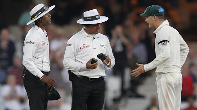 Australia's captain Michael Clarke (R) talks with umpires Aleem Dar (C) and Kumar Dharmasena (L) before play was stopped (AFP)