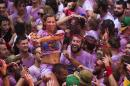 A reveler throws wine during the launch of the 'Chupinazo' rocket, to celebrate the official opening of the 2015 San Fermin fiestas in Pamplona, Spain, Monday, July 6, 2015. Revelers from around the world turned out here to kick off the festival with a messy party in the Pamplona town square, one day before the first of eight days of the running of the bulls. (AP Photo/Andres Kudacki)