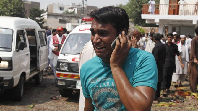 A man uses his mobile phone as he mourns the death of his relatives at the site of a blast at a church in Peshawar