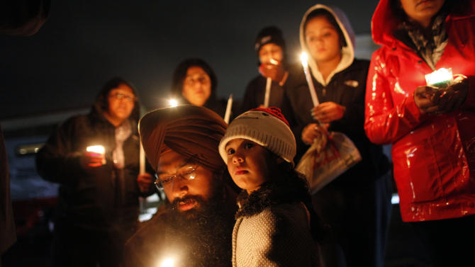 Eknoor Kaur, 3, stands with her father Guramril Singh during a candlelight vigil outside Newtown High School before an interfaith vigil with President Barack Obama, Sunday, Dec. 16, 2012, in Newtown, Conn. A gunman walked into Sandy Hook Elementary School in Newtown Friday and opened fire, killing 26 people, including 20 children. (AP Photo/Jason DeCrow)
