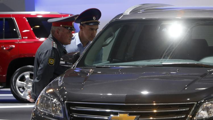 Policemen look at a Chevrolet car during the Moscow International Automobile Salon in Krasnogorsk outside Moscow