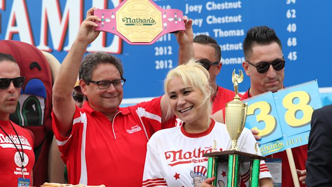 Miki Sudo, second from right, holds her trophy and smiles after winning the Nathan's Famous Fourth of July International Hot Dog Eating Contest women's competition Saturday, July 4, 2015, at Coney Island in the Brooklyn borough of New York. Sudo ate 38 hot dogs and buns in 10 minutes. (AP Photo/Tina Fineberg)(AP Photo/Tina Fineberg)