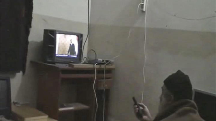 "FILE - This undated image from video seized from the walled compound of al-Qaida leader Osama bin Laden in Abbottabad, Pakistan and released by the U.S. Department of Defense shows a man identified by the U.S. government as Osama Bin Laden in front of a television. A new book due out Tuesday, Oct. 16, 2012 says President Barack Obama hoped to put Bin Laden on trial if he had surrendered during a U.S. raid. Author Mark Bowden quotes the president as saying he thought he could make a strong political argument for giving bin Laden the full rights of a criminal defendant, to show U.S. justice applies even to him. In ""The Finish,"" Bowden writes, however, that Obama said he expected the terror leader to go down fighting. (AP Photo/Department of Defense, File)"