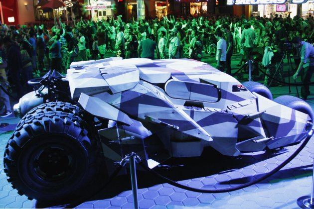 "A crowd of people stand near a Camo Tumbler Batmobile parked outside a midnight premiere of ""The Dark Knight Rises"", the final instalment of Christopher Nolan's Batman trilogy, in Universal City, California, July 19, 2012.  REUTERS/Jonathan Alcorn (UNITED STATES - Tags: ENTERTAINMENT)"