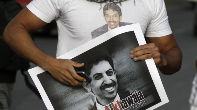 FILE - In this Monday, March 28, 2012 file photo, a Bahraini anti-government demonstrator wears a T-shirt and carries a placard with pictures of Abdulhadi al-Khawaja, as he and others walked toward a sit-in, in Abu Saiba, Bahrain, in support of the jailed opposition rights activist, who is on his 46th day of a hunger strike. A lawyer representing Bahraini hunger striker Abdulhadi al-Khawaja says the activist will end his strike Monday, May 28, 2012, 110 days after he began refusing food. Attorney Mohamed al-Jishi said that al-Khawaja decided to begin eating again because his strike succeeded in bringing attention to the cause of Bahraini protesters agitating for political change. (AP Photo/Hasan Jamali, File)