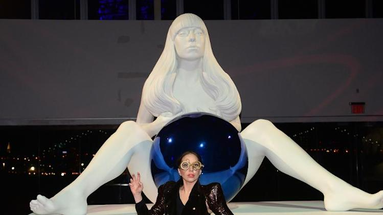 "US singer Lady Gaga poses in front of a statue by artist Jeff Koons, during the launch of her new album ""ARTPOP"" in New York, November 10, 2013"