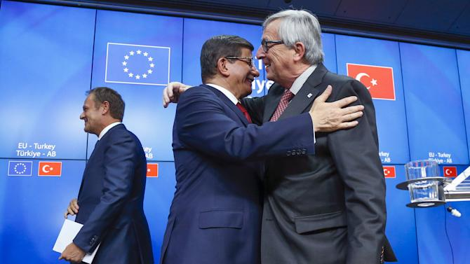 Turkish Prime Minister Ahmet Davutoglu and European Commission President Jean Claude Juncker greet each other while European Council President Donald Tusk leaves the stage after a news conference following a EU-Turkey summit in Brussels, Belgium
