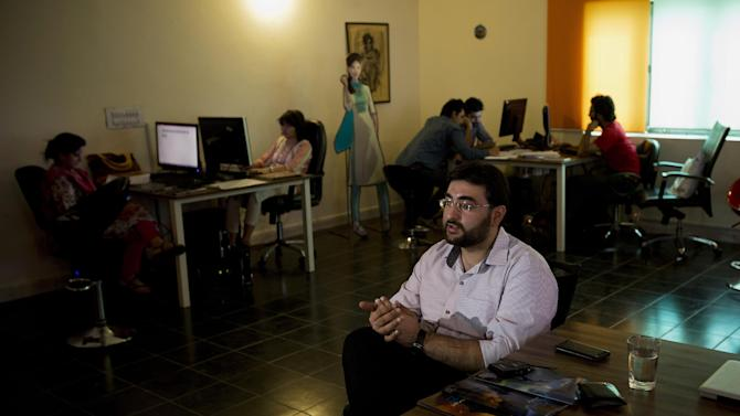 In this photo taken Monday, June 8, 2015, Gauher Aftab, a comic book author, talks about his project called Counter-extremism Art during an interview with The Associated Press in Lahore, Pakistan. Aftab, 31, now works with a group called CFXcomics, which aims to counter extremist propaganda. His English comic book has been translated into Urdu. (AP Photo/B.K. Bangash)