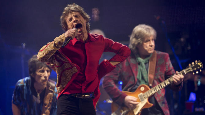 CORRECTING IDENTITY TO MICK TAYLOR AT RIGHT - Mick Jagger, center, Ronnie Wood, left, and Mick Taylor at right, of British rock band the Rolling Stones perform on the Pyramid main stage at Glastonbury, England, Saturday, June 29, 2013. Thousands of music fans have arrived for the festival to see headliners, Arctic Monkeys, Mumford and Sons and the Rolling Stones. (Photo by Joel Ryan/Invision/AP)