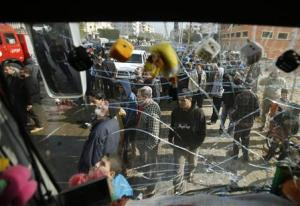 Palestinians are pictured through the damaged windscreen of a bus at the scene of an Israeli air strike in the northern Gaza Strip
