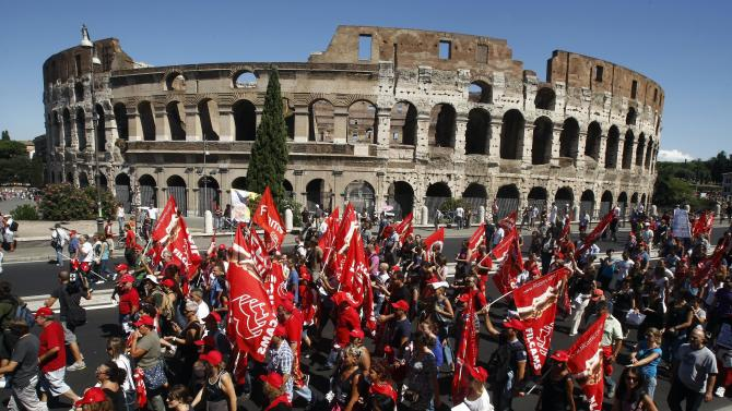 Demonstrators march past the Colosseum during a general strike in Rome, Tuesday, Sept. 6, 2011. With Silvio Berlusconi's government under increasing pressure to produce credible measures to balance the budget, a strike by Italy's largest labor union against an austerity package shut down air, land and sea transport, stalled manufacturing and curtailed government services throughout the country on Tuesday. Susanna Camusso, head of the left-leaning CGIL, said the euro 45.5 billion ($68 billion) austerity package needs to be thrown out and substituted with fairer measures. (AP Photo/Pier Paolo Cito)