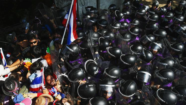 Anti-government protesters clash with riot police during a mass rally outside the house of PM Shinawatra in Bangkok
