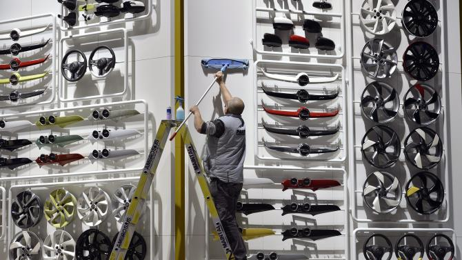 A worker cleans at the Opel booth during the last preparations prior to the opening of the press preview days at the 83nd Geneva International Motor Show in Geneva, Switzerland, Saturday, March 2, 2013. The Motor Show will open its gates to the public from March 7 to 17, presenting more than 260 exhibitors and more than 130 world and European premieres. (AP Photo/Keystone, Martial Trezzini)