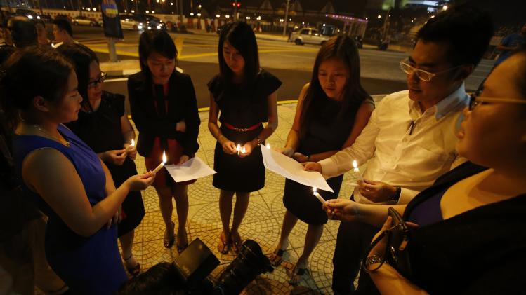 Malaysian ethnic Chinese sing songs as they hold a candlelight vigil for the passengers of Malaysia Airlines MH370 near Independence Square in Kuala Lumpur