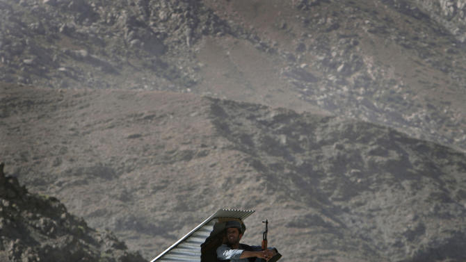 An Afghan police officers sits on the roof of a building prior to the arrival of dignitaries attending a ceremony to mark the transfer of authority from NATO-led International Security Assistance Forces to Afghan forces in Bazarak, Panjshir province, north of Kabul, Afghanistan, Sunday, July 24, 2011. (AP Photo/Musadeq Sadeq)