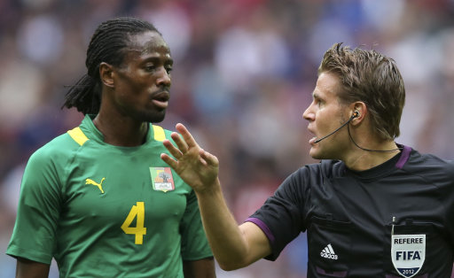 Senegal's Abdoulaye Ba speaks with referee Felix Brych after he got a red card during their men's preliminary first round Group A soccer match against Uruguay at the London 2012 Olympic Games in the Wembley Stadium in London